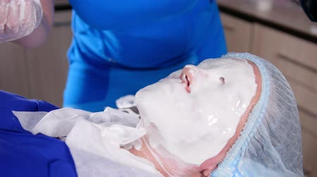 活性化させる : Beauty clinic. Young woman gets a cosmetology treatment. Smearing a white anti-aging liquid mask on the face. 動画素材