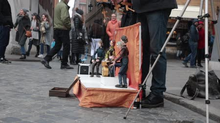 marionetka : POLAND, WARSAW 9-11-2018: Puppets plays instruments on the little stage. People control the marionettes. People watching the performance