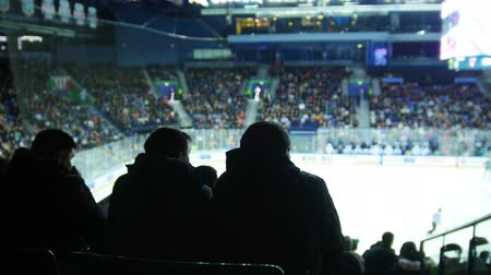 вратарь : A group of silhouettes of young people watching hockey match. Filled Tribunes