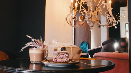 kaplanmış : A sweet breakfast. A piece of blackberry cake and cup of coffee on the table. Great interior Stok Video
