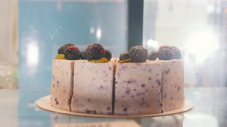 amoras : A blackberry cake behind the shop window. Blackberries on the top of the cake.