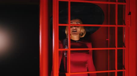old radio : A woman in big retro hat and red dress singing behind the red glass door