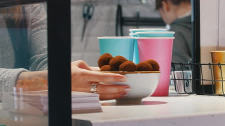 kaplanmış : Serving a bowl with chocolate truffles on the checkout Stok Video