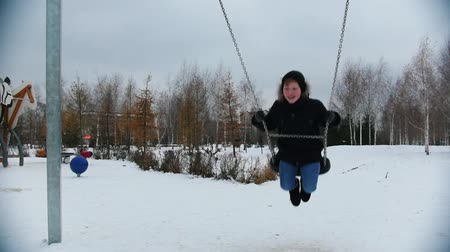 śnieżka : A young boy swinging on the playground Wideo