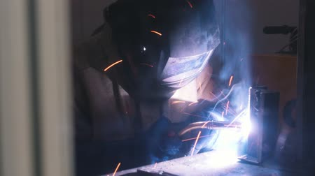 spawanie : Welding process. A welder in helmet doing his job in the dark. Smoke and sparks