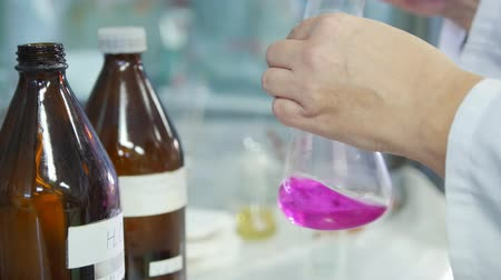 banka : A woman mixing purple liquid with chemical substance into a flask