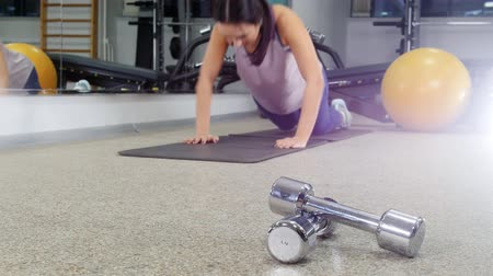 volleyball players : Training. A young woman doing push ups. Dumbbells on the foreground Stock Footage