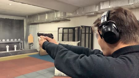 пистолеты : Man aims, holding a gun at a shooting gallery, shooting range.