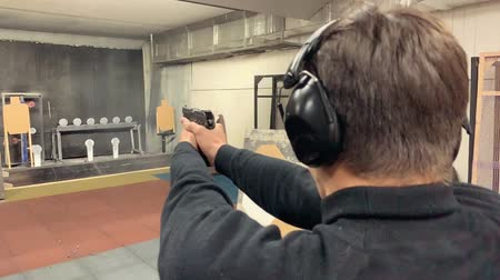 atirador : Young man aims, holding a gun at a shooting gallery, shooting range.