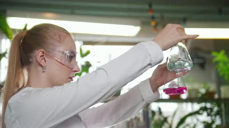banka : Chemical laboratory. Young blond woman pouring the liquid from one flask to another Dostupné videozáznamy