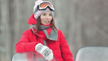 śnieżka : Winter. A young woman in red down jacket stand leaning on the snowmobile with a hand Wideo