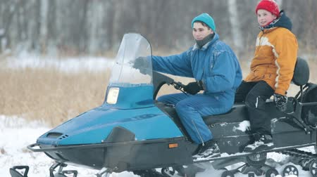 extreme weather : Winter. A young man carries a little boy on a snowmobile. Riding.