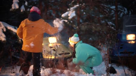 baharatlı alman sosisi : Winter forest. Young family playing with snow in the woods by the fire