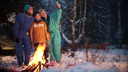 roasting : Winter forest. Young family taking a photo in the woods by the fire