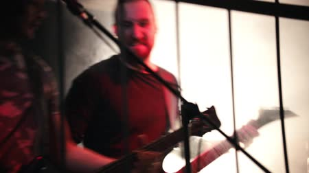 rockstar : Guitarist enthusiastically playing on a stage on a black guitar. Smoky stage Stock Footage