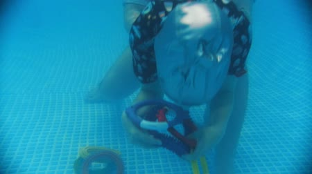 pediatrie : Water rehabilitation procedure with child with cerebral palsy. A kid grabbing a toy from the bottom. Underwater