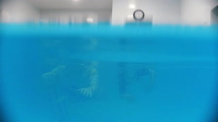rehabilitasyon : Water rehabilitation procedure with child with cerebral palsy. A baby swimming with instructor Stok Video
