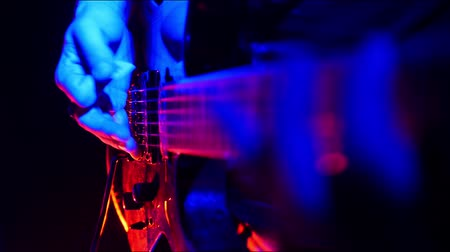 yüksek sesle : Guitarist tunes and start playing on his guitar in bright neon lighting.