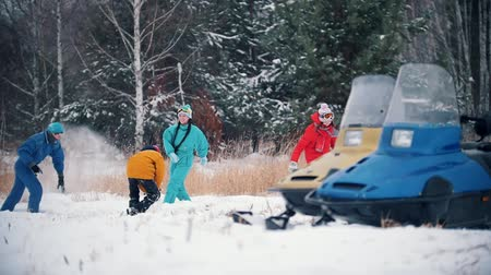 motoslitta : Winter forest. Young happy family in colorful clothes having fun playing snowballs near the snowmobiles. Slow motion