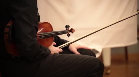 rehearsing : Chamber orchestra. A man sitting on the chair holding a violin and a bow