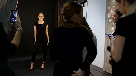 altura : Young woman model having a photo session in the studio. Shooting the model in black clothes. Shooting in full height. Another models shooting on their phones Stock Footage