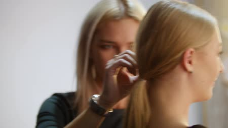 стегать : RUSSIA, KAZAN. 14-12-2018: Makeup artist touching up ponytail.