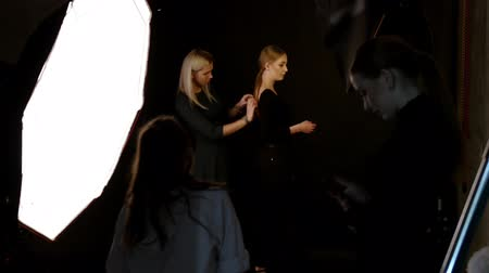 oturum : RUSSIA, KAZAN. 14-12-2018: Young woman model having a photo session in the studio.An assistant corrects dress