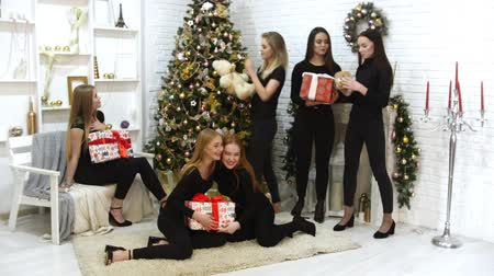 peluş : Six beautiful models taking a photo together in the studio Holding christmas gifts in the boxes. Smiling and having fun Stok Video