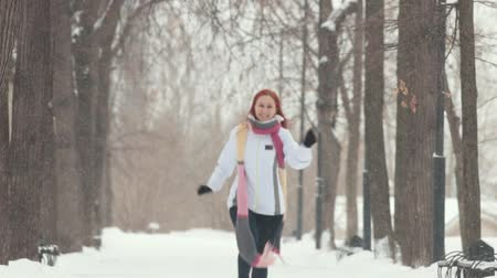 imbir : Winter park. A smiling woman with bright red hair skipping closer to the camera Wideo