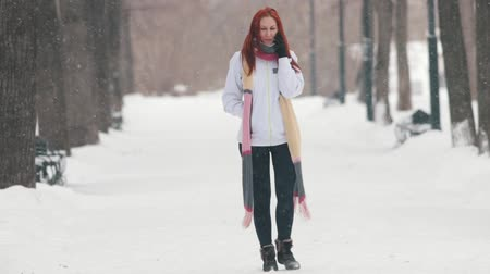 замораживать : Winter park. A woman with bright red hair and a long scarf talking on phone Стоковые видеозаписи
