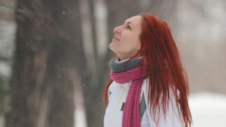 imbir : Winter park. A woman with bright red hair standing on the sidewalk. Catching snowflakes with a mouth Wideo