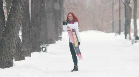 śnieżka : Winter park. A cheerful woman with bright red hair standing on the sidewalk, making a snowball and throwing it forward Wideo