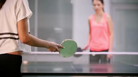 подача : Ping pong playing. Young woman innings the ball, her opponent fails and the woman catches the ball with a hand