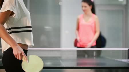 подача : Young woman innings the ball, her opponent fails. Table tennis