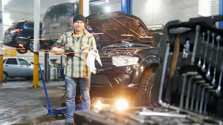 wipe off : Car service. Mechanic man standing by the car and wipes off the tool Stock Footage