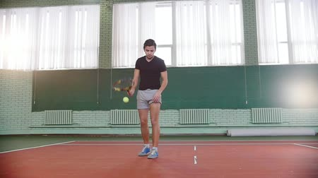 isabet : Training on the tennis court. Young man gets the ball out of his pocket and hitting the floor with it