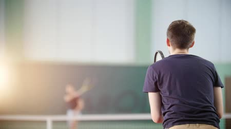 isabet : Training on the tennis court. Two young men playing tennis. Hitting the ball with a racket. Back view