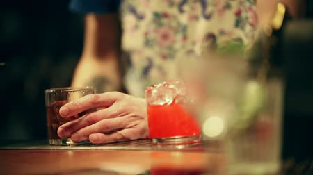 remoção : Bartender working. Mixing an alcoholic cocktail in the glass. Adding an ice Stock Footage