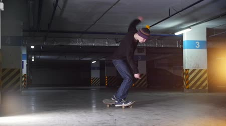 kickflip : Underground parking lot. A young man skateboarding. Training his skills in kickflip trick