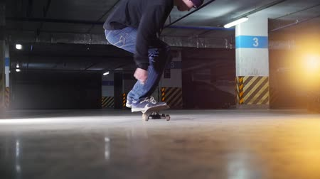 parkoló : Underground parking lot. A young man skateboarding. Making a spin and continue skating