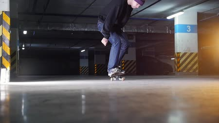 kickflip : Underground parking lot. A young man skateboarding. Practicing the kickflip trick