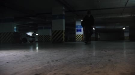 paten yapma : Underground parking lot. A young man skateboarding. Practicing his skating skills Stok Video