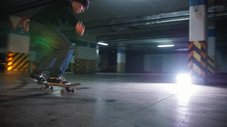 deskorolka : Underground parking lot. A young man skateboarding. Practicing the ollie trick Wideo
