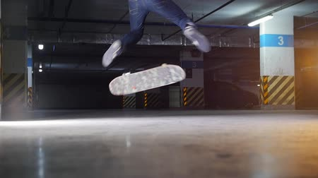 kickflip : Underground parking lot. A young man skateboarding. Practicing complicated trick