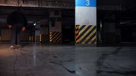 paten yapma : Underground parking lot. A young man practicing skateboarding