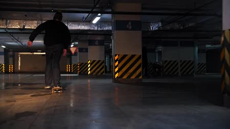 paten yapma : Underground parking lot. A young man practicing skateboarding skills Stok Video