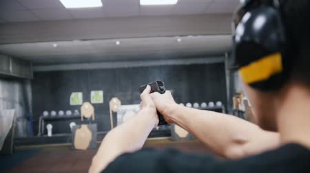 atirar : Shooting gallery. A young man in headphones shooting with a firearms. A smoking gun