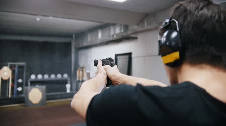 картридж : Shooting gallery. A young man in black t-shirt shooting with a firearms.