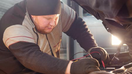 круглолицый : Car service. Thick ginger mechanic man checks the voltage with a multimeter