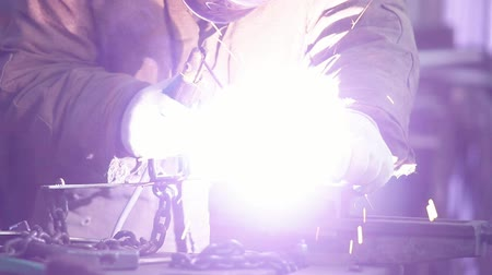 сварщик : Welding process. A man worker attaching a small detail by welding